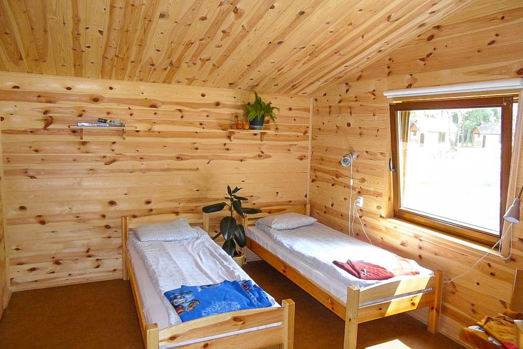 Wnętrze domku wypoczynkowego w Powsinie. Dwa pojedyncze łóżka