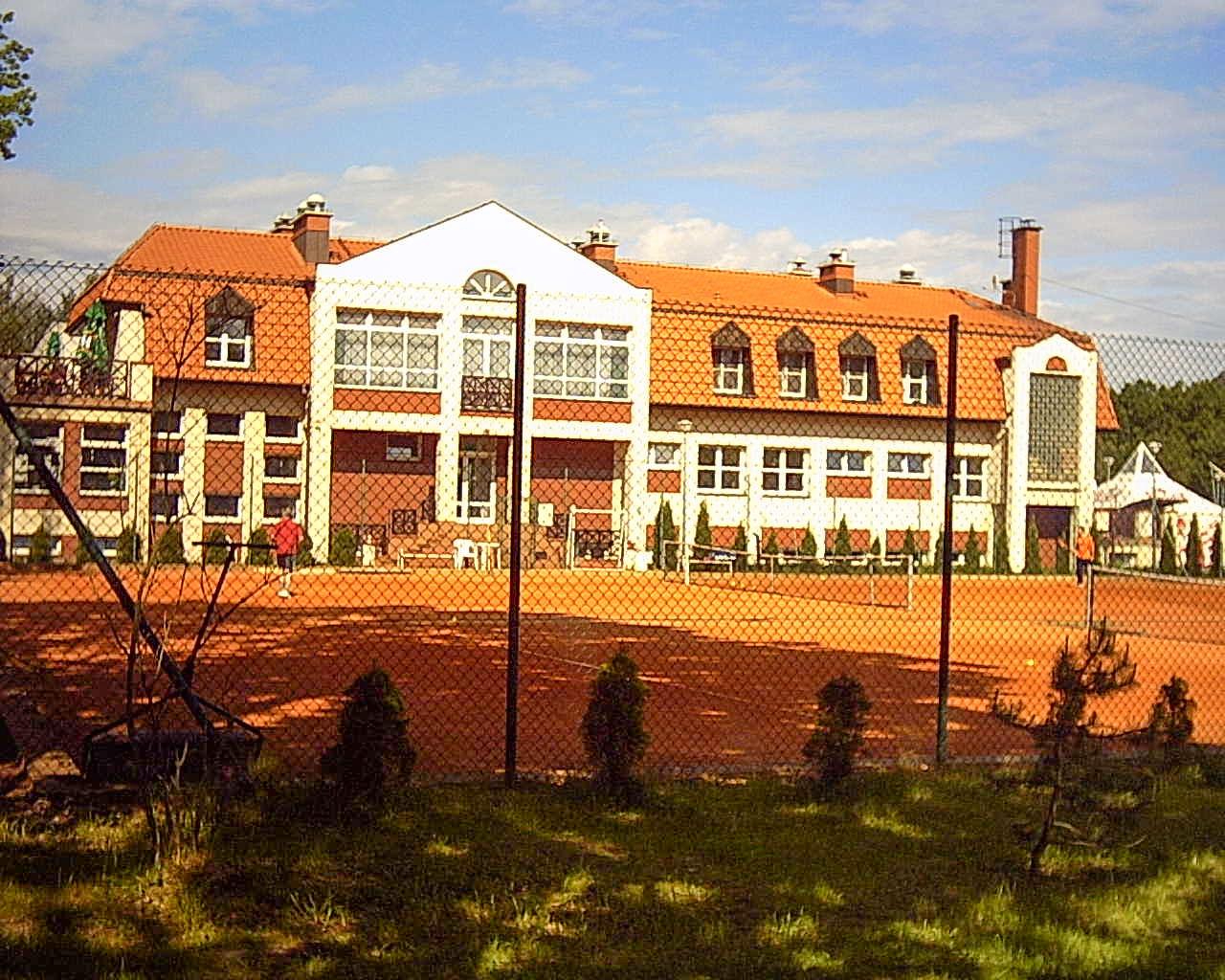 widok na korty tenisowe ceglane i budynek pawilonu rekreacyjno-sportowego