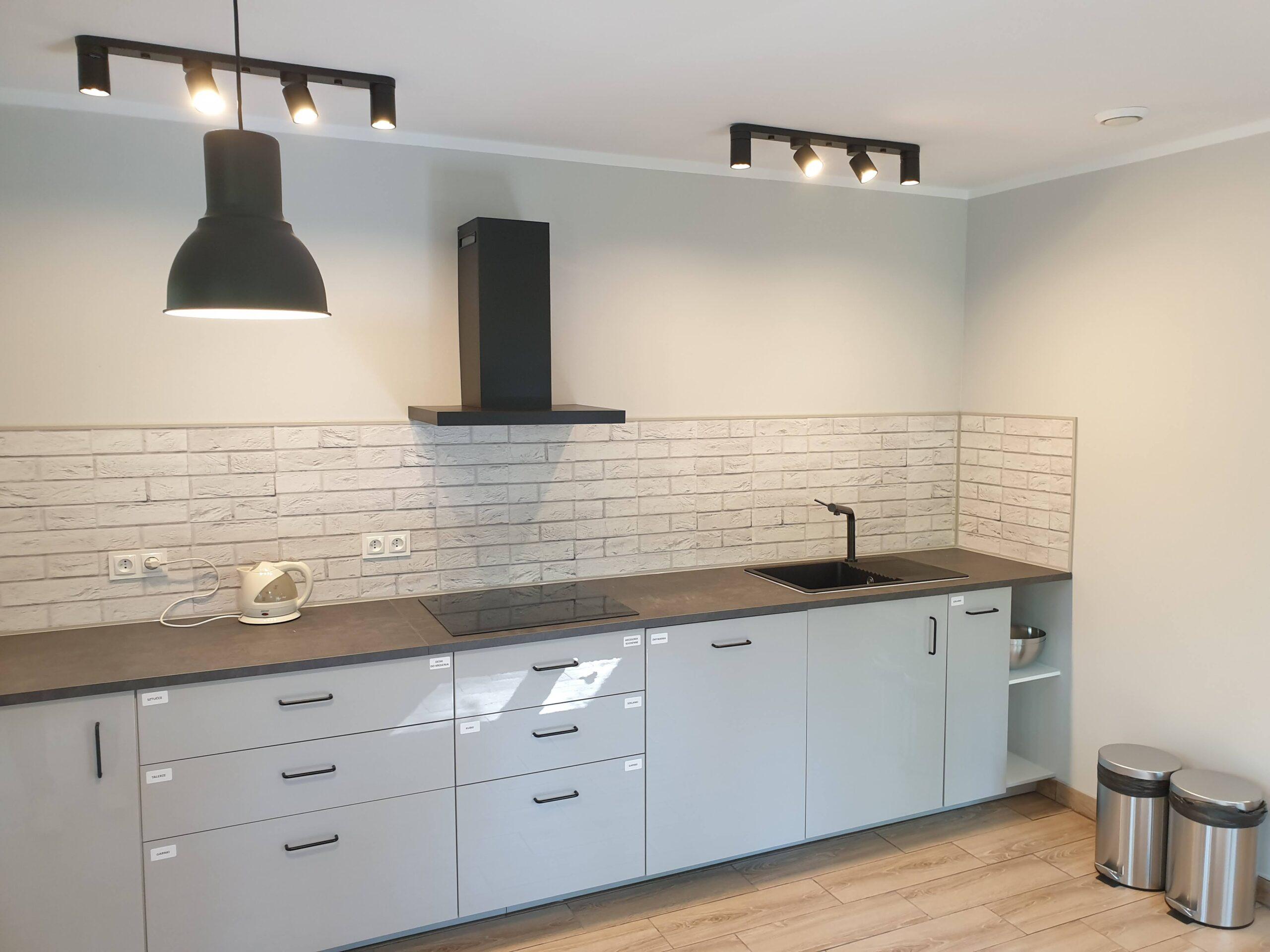 zdjęcie obrazujące wygląd kuchni w ośrodku wypoczynkowym tj. szafki, okap, płytę indukcyjną